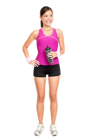 Asian fitness woman model standing in sporty gym clothing smiling happy holding water bottle.