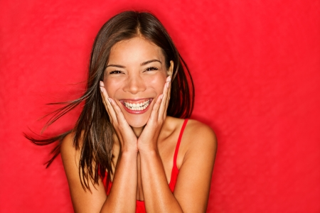 Foto de Happy girl excited. Young woman smiling very happy surprised holding head being amazed on red background.  - Imagen libre de derechos