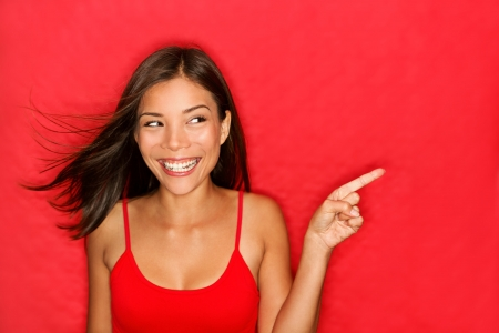 woman pointing showing on red background looking to the side. の写真素材