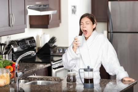 Yawning coffee woman in morning standing by kitchen table at home.