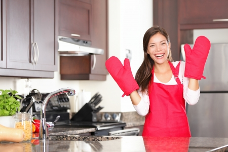 Happy baking cooking woman standing in her new kitchen smiling cheerful wearing apron and oven mitts ready to bake.の写真素材