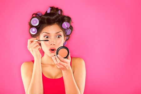 Makeup mascara woman with hair rollers getting ready looking in pocket mirror  Funny image of beautiful funky trendy young mixed race asian caucasian female fashion model putting makeup on pink background  Mixed race Caucasian   Asian girl