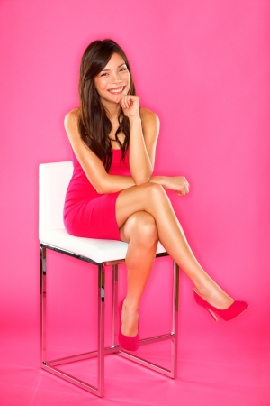 Photo for Women sitting portrait on pink  Woman sitting on chair in full length studio portrait on pink background  Beautiful smiling happy Asian Chinese   Caucasian  - Royalty Free Image