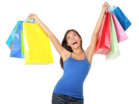 Happy shopping woman excited and cheerful in joyful bliss. Shopper holding many colorful shopping bags isolated on white background in studio. Elated beautiful mixed race Caucasian / Asian Chinese female model.