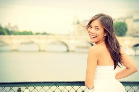Paris woman laughing joyful and candid in Paris on brige on river Seine  Fresh energetic young mixed race Asian Caucasian female model joyful