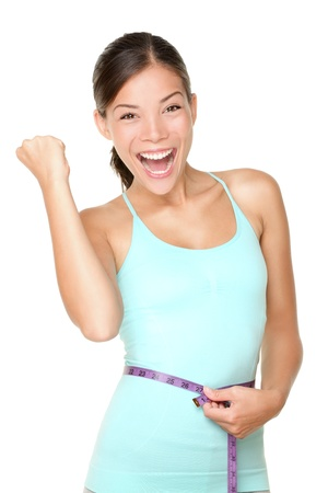 Weight loss concept woman smiling happy excited holding measuring tape around waist  Energetic portrait of sport fitness model isolated on white background  Mixed race Caucasian   Asian woman
