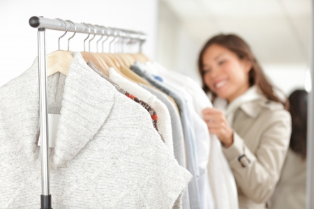 Photo pour Clothing  Woman shopping clothes in store looking at clothing rack  Focus on winter sweater in foreground  - image libre de droit