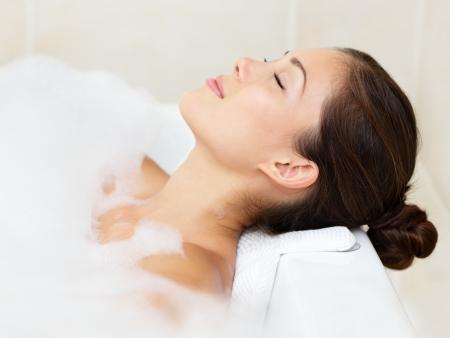 Bath woman relaxing bathing in bathtub with bath foam