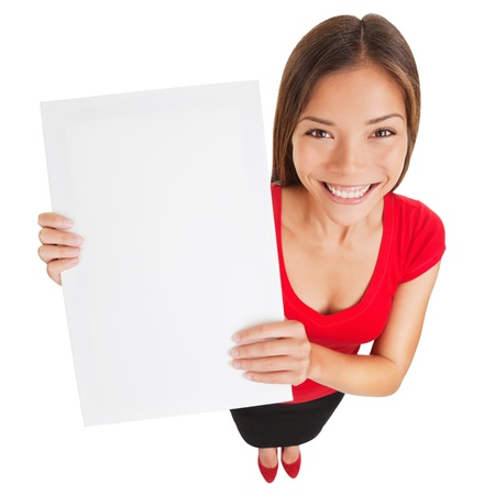 Sign woman showing blank poster billboard  Portrait in high angle perspective of beautiful charming woman with lovely smile holding up a blank white sign for your attention isolated on white background