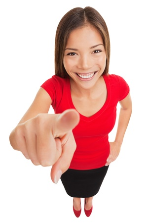 Pointing woman  Attractive smiling woman pointing directly at the camera with her finger as she makes her selection or identifies a person, funny high angle full length portrait isolated on white