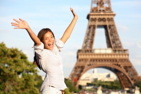 Happy tourist on travel holidays cheering joyful with arms raised up excited at Paris Eiffel Tower