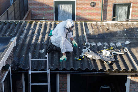 Photo for Professional asbestos removal. Men in protective suits are removing asbestos cement corrugated roofing - Royalty Free Image