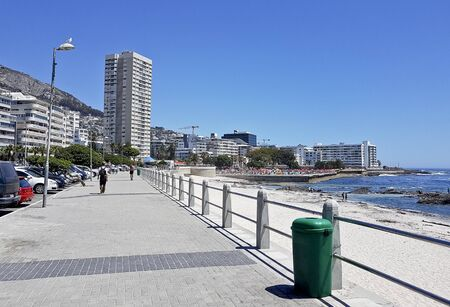 Photo pour Mountains, hotels and deep blue water with waves at the Sea Point, beach promenade in Cape Town South Africa. - image libre de droit