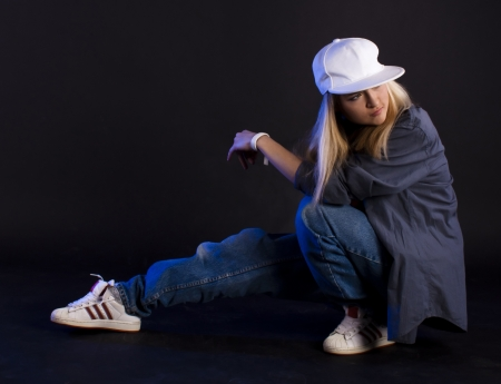 Modern dance, hip hop girl dancer on a black background.