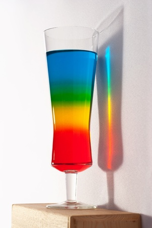 Photo pour A colorful, layered cocktail  with beautiful rainbow reflection on the wall - image libre de droit
