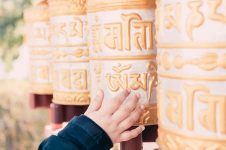 Photo pour Group of golden prayer wheels typical of Buddhist temples moved by a child's hand. - image libre de droit