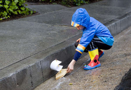 Young boy playing with toy boat in the rain wearing rain slickers and golashes.