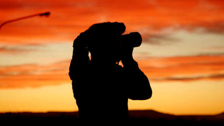 Photo pour A profile of a photorapher with a colored sky in background - image libre de droit