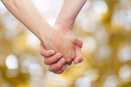 Photo pour couple holding hands  on glittering background.background with bokeh defocused lights - image libre de droit
