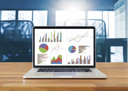 Photo pour Laptop on wooden table showing charts and graph against office background ,Analysis Business Accounting, Statistics Concept. - image libre de droit