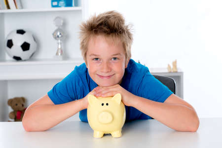 smiling boy in blue shirt with piggy-bank