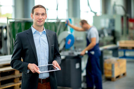 Photo for young boss with worke in the background in his factory - Royalty Free Image