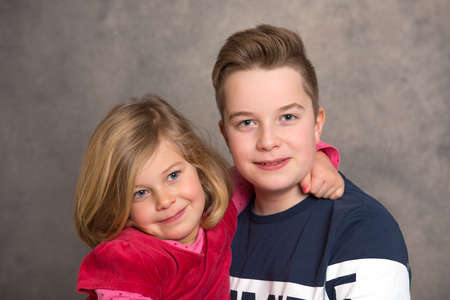 brother and sister together in front of gray background