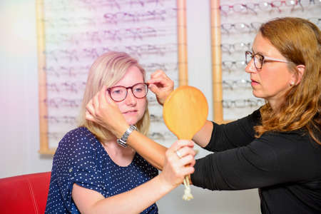 in optician shop- young blond woman selecting new glasses