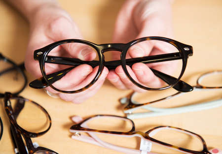 Photo pour in optician shop- glasses for sale and one glasses in hand - image libre de droit