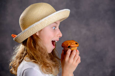 nice girl with blond hair in white dress and straw hat eating muffin