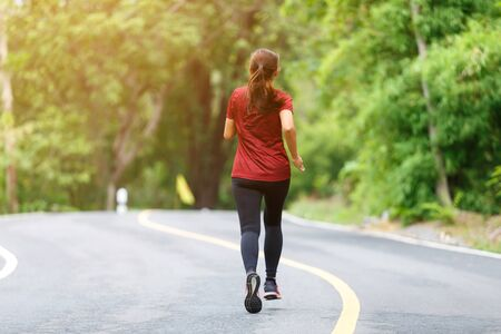 Foto de Back of woman runner and runing at the road surround with green forest. - Imagen libre de derechos