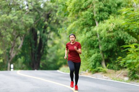 Photo for Front of woman runner and runing with full speed at the road surround with green forest. - Royalty Free Image