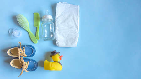 Foto de Baby care accessories, newborn baby diaper, pacifier, comb and hair brush, bottle, little boy shoes and toy on a blue background. Wish list or shopping overview for pregnancy, baby shower concept. - Imagen libre de derechos