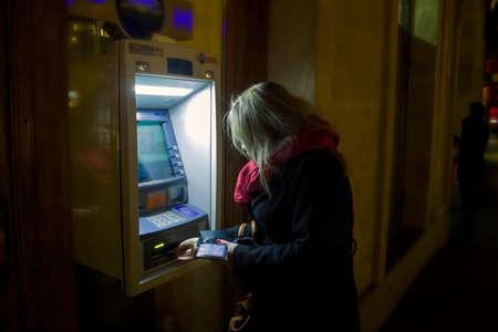 Photo pour Krakow, Poland - October 25, 2014: A woman using ATM at night in winter - image libre de droit