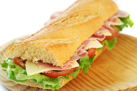 baguette sandwich with lettuce, tomatoes, ham, and cheese on a wood dish
