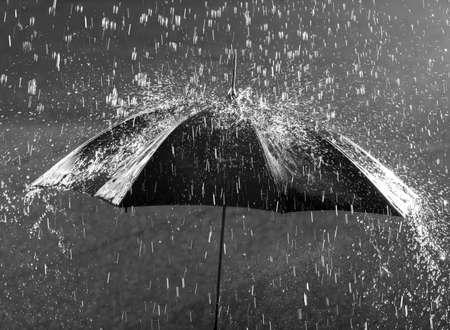 Black and white photo of umbrella in heavy rain