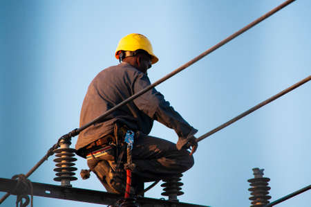 Photo pour Electric lineman in a yellow helmet working with clamps at heights on the cables of the streets, above a pole secured by belts - image libre de droit