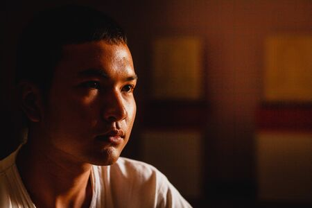 Photo pour Sad young man thinking in dork room,Low key style. - image libre de droit