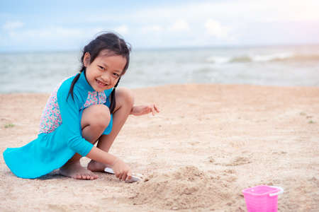 Photo pour Happy little girl playing with sand on tropical beach - image libre de droit