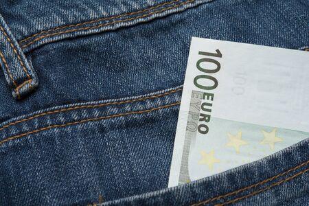 Photo pour A hundred euro note in the back pocket of a blue jeans - image libre de droit