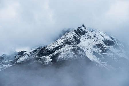 Snowed Mountain peaks hidden in clouds in Himalayas. Travel to Nepal