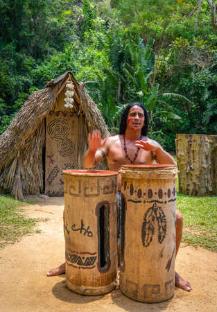 Man performing for tourists as Taino indian near Indian Cave orCueva del Indio in Vinales, Cuba. Spring 2019. Playing drums and singing songs