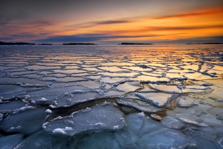 Morning dawn with frozen ice floats in sea coast