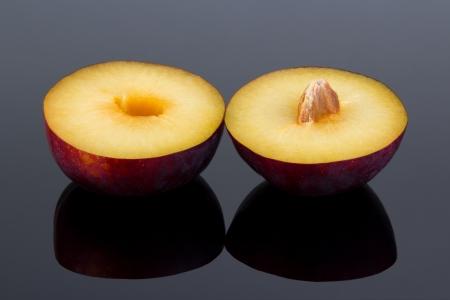 Halved plum fruit on reflective dark surface