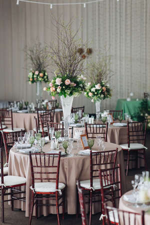Photo pour Beautiful composition with flowers on the tables and candles for guests at a wedding or a birthday party. - image libre de droit
