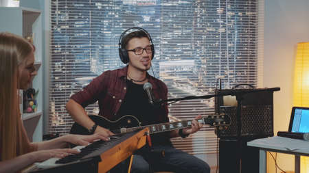 Recording hit song in home studio: young man in headphone singing and playing guitar while the pianist accompanying him. There is different recording equipment in the room.