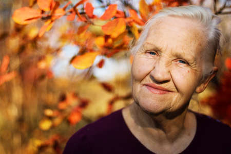 Portrait of the smiling elderly woman  on the autumn background