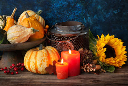 Autumn thanksgiving decor with candle, sunflower and pumpkin