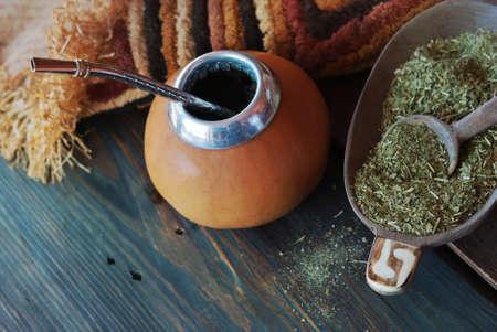 Foto de Yerba mate-South American tea, dried leaves in wooden bowl with a wooden mate calabash with tea. Selective focus - Imagen libre de derechos