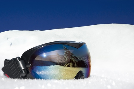 Photo pour protective eyewear for winter sports and recreation on the background of snowy mountains and blue sky - image libre de droit